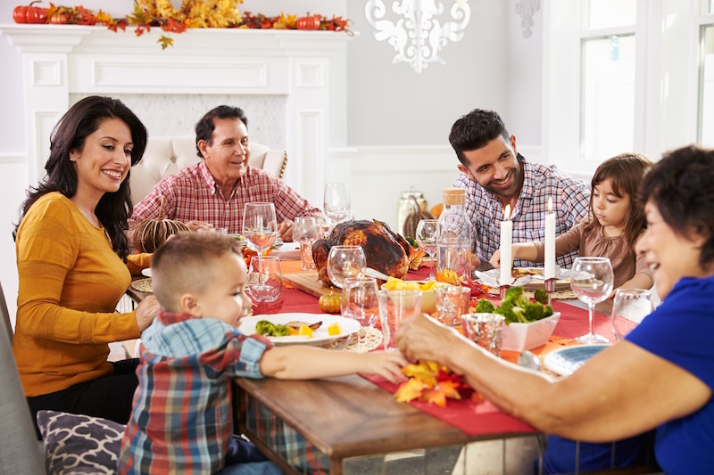 Family eating Thanksgiving dinner, smiling with beautiful, healthy, white teeth
