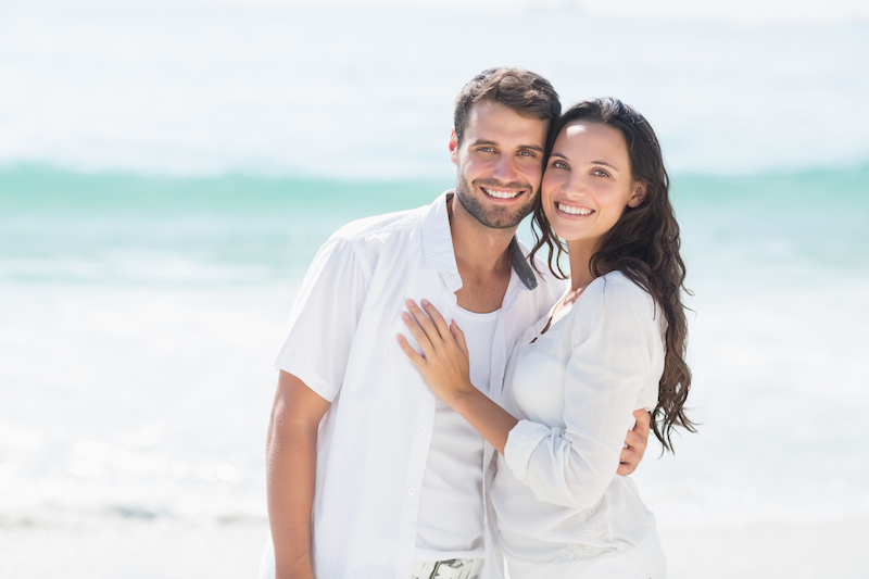 Smiling couple on beach, both with beautiful teeth because of regular dental visits